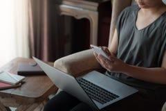 Femme à l'aide de l'ordinateur portable dans la maison Photographie stock