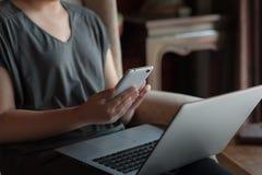 Femme à l'aide de l'ordinateur portable dans la maison Photos stock