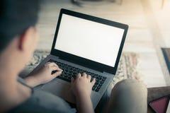 Femme à l'aide de l'ordinateur portable dans la maison Images stock