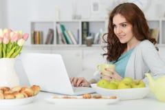 Femme à l'aide de l'ordinateur portable à la table Photo stock