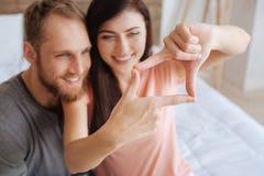 Femme à l'aide de ses doigts pour encadrer des visages de couples images libres de droits