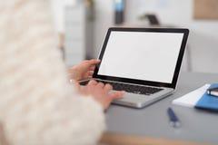 Femme à l'aide de son ordinateur portable avec l'écran blanc vide Image stock