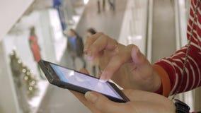 Femme à l'aide de son téléphone intelligent dans le centre commercial, avant Noël banque de vidéos