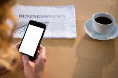 Femme à l'aide de son téléphone portable avec la tasse de journal et de café sur la table Photographie stock