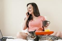 Femme à l'aide de son téléphone portable et prenant le petit déjeuner photos stock