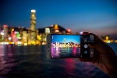 Femme à l'aide de son téléphone portable pour prendre la photo de la vue de ville Photographie stock libre de droits