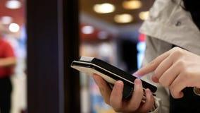 Femme à l'aide de son téléphone portable sur le beau fond lumineux brouillé à l'intérieur du restaurant de Mcdonalds clips vidéos
