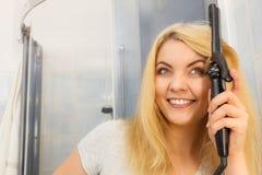 Femme à l'aide du bigoudi de cheveux photo libre de droits