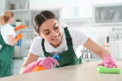 Femme à l'aide du chiffon et du pulvérisateur pour la table de nettoyage avec le collègue photographie stock