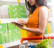 Femme à l'aide du comprimé au magasin photographie stock