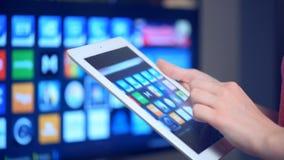 Femme à l'aide du comprimé avec Smart TV banque de vidéos