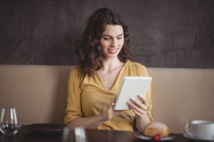 Femme à l'aide du comprimé numérique dans le restaurant photos libres de droits