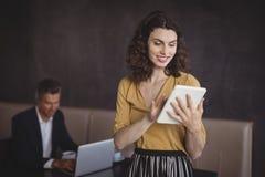 Femme à l'aide du comprimé numérique dans le restaurant photos stock