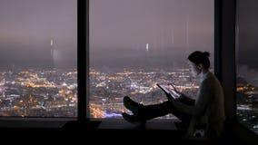 Femme à l'aide du comprimé numérique noir la nuit banque de vidéos