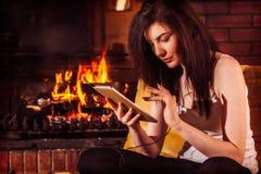Femme à l'aide du comprimé numérique se reposant par la cheminée Photos stock
