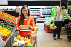 Femme à l'aide du comprimé numérique tout en faisant des emplettes dans le supermarché photo libre de droits