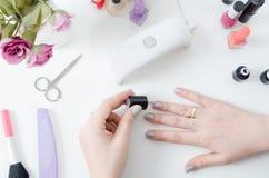 Femme à l'aide du dessiccateur de lumière UV Manucure, concept de salon de station thermale photos stock
