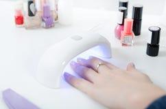 Femme à l'aide du dessiccateur de lumière UV Manucure, concept de salon de station thermale images stock