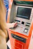 Femme à l'aide du distributeur automatique de billets d'atmosphère image libre de droits