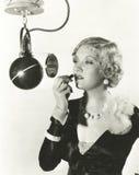 Femme à l'aide du miroir de microphone Images stock