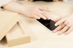 Femme à l'aide du nouveau smartphone près de la boîte photos libres de droits