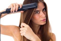 Femme à l'aide du redresseur de cheveux Photos stock
