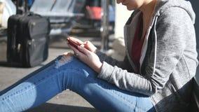 Femme à l'aide du smartphone dans le salon de attente d'aéroport Main femelle avec le téléphone intelligent sur le terminal penda banque de vidéos