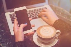 Femme à l'aide du smartphone et de l'ordinateur portable tout en appréciant le café au t Image libre de droits