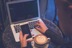 Femme à l'aide du smartphone et de l'ordinateur portable tout en appréciant le café au t Images stock