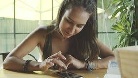 Femme à l'aide du smartphone et souriant en café Beau jeune travailler femelle occasionnel au téléphone portable banque de vidéos