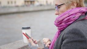 Femme à l'aide du smartphone à la rivière clips vidéos