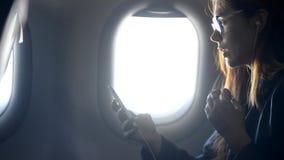 Femme à l'aide du smartphone moderne et parlant dans l'avion banque de vidéos
