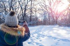Femme à l'aide du smartphone pour prendre la photo du paysage d'hiver au coucher du soleil photos stock