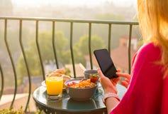 Femme à l'aide du téléphone au petit déjeuner sur le balcon Image libre de droits
