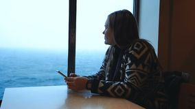 Femme à l'aide du téléphone dans la carlingue de bateau banque de vidéos