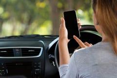 Femme à l'aide du téléphone dans la voiture sur la route photos stock