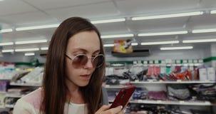 Femme à l'aide du téléphone dans le magasin clips vidéos