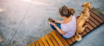 Femme à l'aide du téléphone dans le parc Photographie stock libre de droits