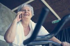 Femme à l'aide du téléphone intelligent dans le gymnase Femme parlant sur Photos libres de droits