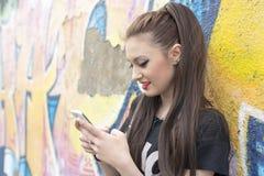 Femme à l'aide du téléphone intelligent sur le fond de graffiti Photo libre de droits