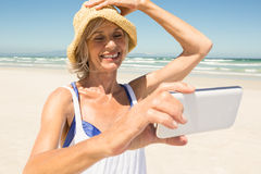 Femme à l'aide du téléphone intelligent tout en se tenant à la plage contre le ciel clair Image libre de droits