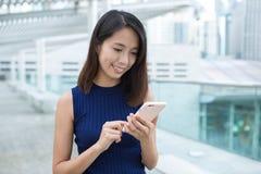Femme à l'aide du téléphone portable à extérieur Photographie stock libre de droits