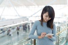 Femme à l'aide du téléphone portable à l'aéroport Images libres de droits