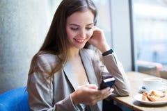 Femme à l'aide du téléphone portable au café Image stock