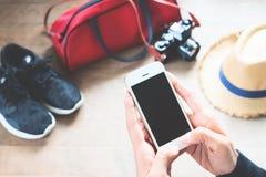 Femme à l'aide du téléphone portable avec des préparations de voyage sur le plancher en bois Photos libres de droits