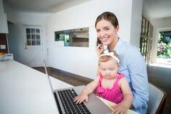 Femme à l'aide du téléphone portable avec le bébé par l'ordinateur portable Images stock