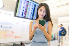Femme à l'aide du téléphone portable dans l'aéroport Images libres de droits