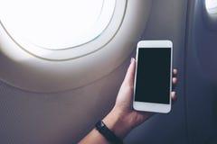 Femme à l'aide du téléphone portable dans l'avion Photos stock
