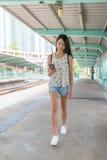 Femme à l'aide du téléphone portable dans la gare légère de Hong Kong image libre de droits