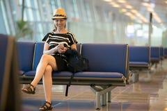 Femme à l'aide du téléphone portable dans le salon de attente d'aéroport Photo libre de droits